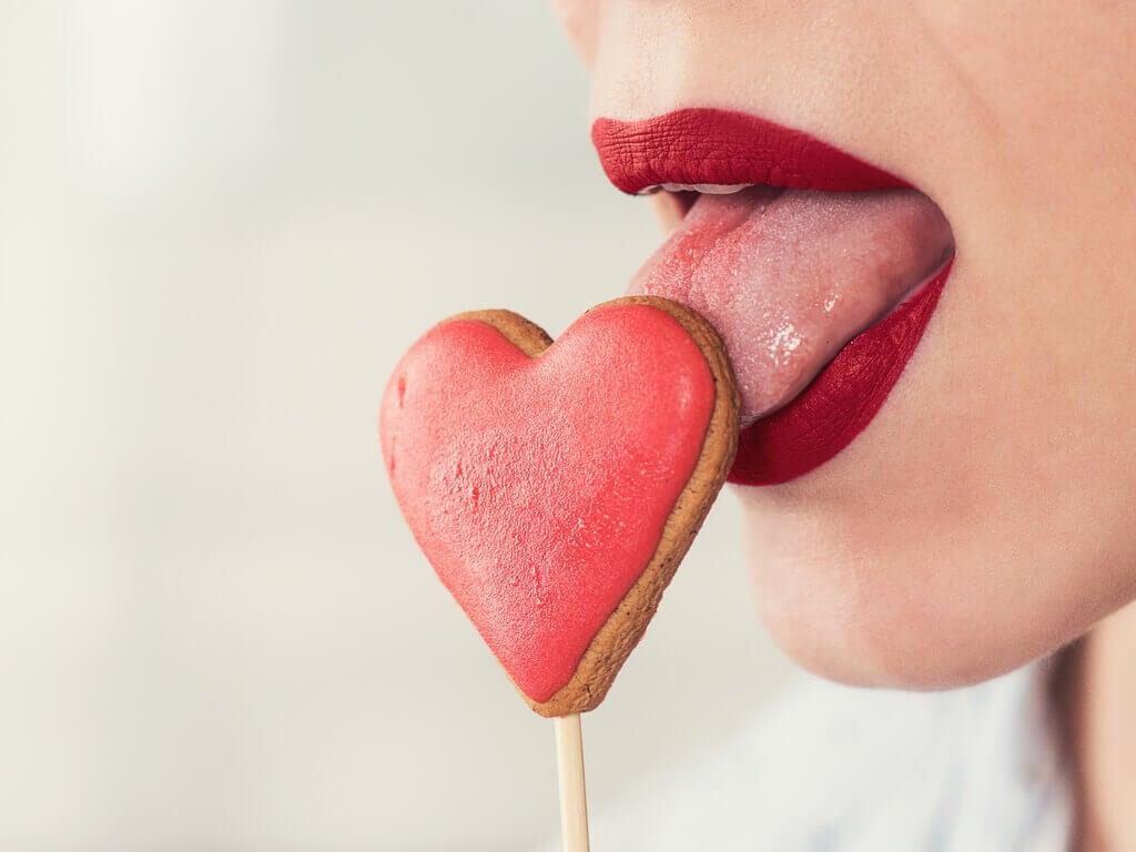 femme léchant une sucette en forme de coeur